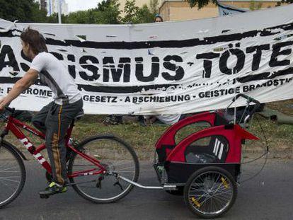 """Un vecino pasa por una pancarta que dice """"El racismo mata"""" montada delante del nuevo centro de refugiados en Berlín este miércoles."""