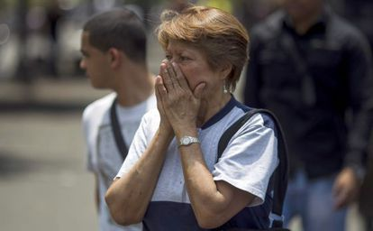 Una mujer se cubre el rostro de los gases lacrimógenos en Caracas.