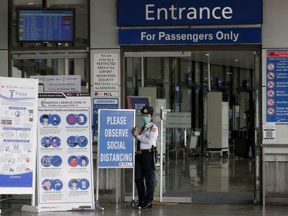 Una agente de seguridad del aeropuerto de Manila, el miércoles junto a las instrucciones de control de la pandemia.