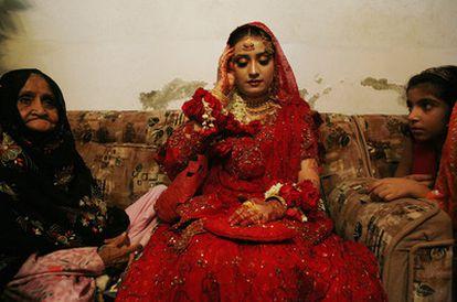 Boda de Aicha (15 años), hija del mulá en la 'madrasa' Jamia Siraj Ul Uloom, Pakistán. La joven novia tiene que aparecer ante los invitados vestida así, llevando joyas de oro, y aguantar con la mirada baja durante horas. Su velo se está moviendo y ella intenta mantanerlo en su lugar, sin moverse. La imagen forma parte de una serie del autor sobre Pakistán.