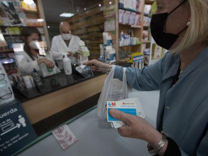 Una mujer compra medicamentos en una farmacia con su tarjeta sanitaria en Madrid, el pasado 2 de junio.