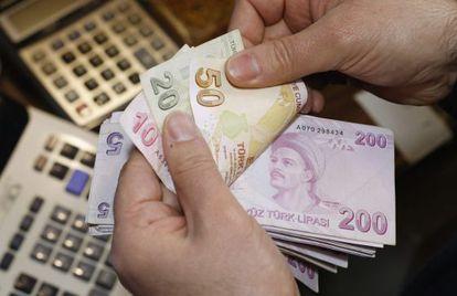 Un hombre cuenta liras en una oficina de Cambio, en Estambul.