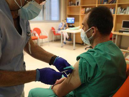 Un trabajador sanitario inyecta una dosis de la de Pfizer-BioNTech contra la covid-19 a otro sanitario en un hospital de Madrid.
