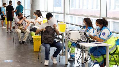 Varias personas reciben la vacuna contra la covid en el punto de vacunación masivo instalado en el Wizink Center de Madrid, el pasado agosto.