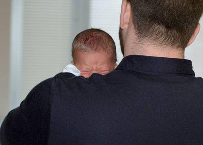 Un padre con su bebé en brazos.