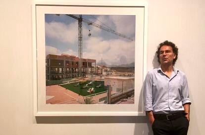 """Txema Salvans junto a la última de las fotografías que ha realizado de su serie 'Perfect Day', que se puede ver en Foto Colectania."""" en una exposición en Foto Colectania"""