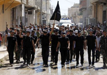 Un grupo de combatientes islamistas ondea su bandera en el funeral por un compañero caído ayer cerca de Alepo.