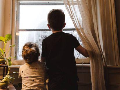 Dos niños miran por la ventana.
