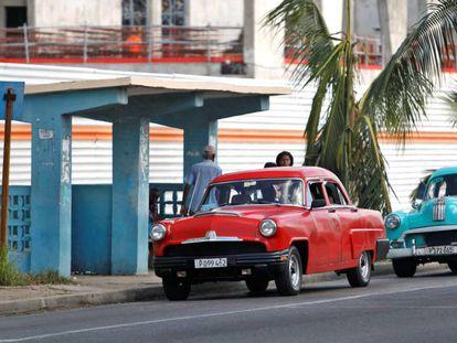 Dos automóviles clásicos pasan frente a una parada de autobus, el miércoles en La Habana (Cuba).