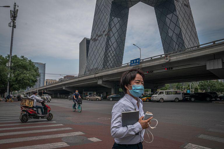 Una mujer con mascarilla pasea frente a la sede de la televisión estatal china, CCTV, uno de los edificios más emblemáticos de Pekín