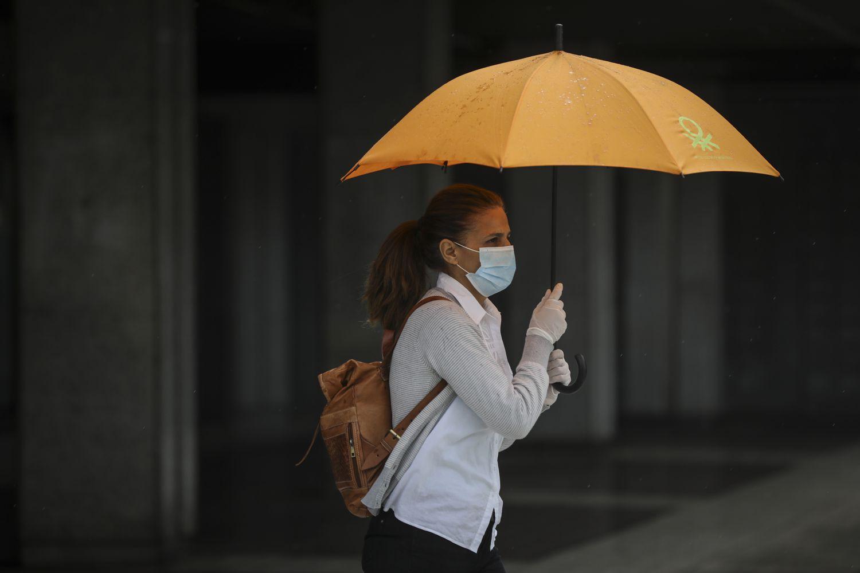 Una mujer se resguarda de la lluvia el pasado día 15 en Sevilla.