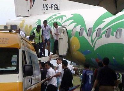 Trabajadores del aeropuerto de Koh Samui ayudan a los pasajeros a bajar del avión.