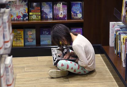 Una niña lee en el aeropuerto de Denver (Colorado)