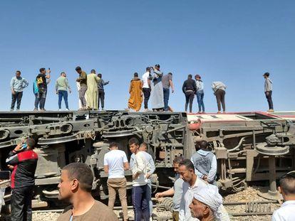 Un grupo de personas sobre un vagón volcado en un accidente de tren en la provincia egipcia de Sohag toman imágenes con sus teléfonos, mientras otros inspeccionan la escena.
