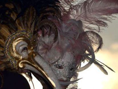 Una pareja portando espectaculares máscaras pasean por Venecia