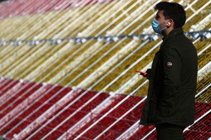 Un hombre con mascarilla ante la bandera gigante de LED en el puente de Juan Bravo en La Castellana de Madrid.