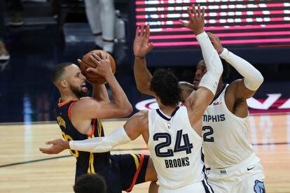 Stephen Curry intenta lanzar ante la oposición de Brooks y Tillman en el partido Warriors-Grizzlies.