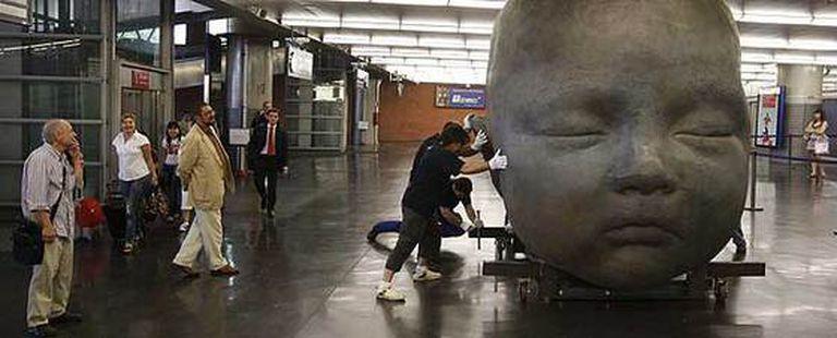 Antonio López, en primer plano a la izquierda,  dirige la instalación de las esculturas en la estación de Atocha.