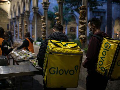 Dos repartidores de Glovo hacen cola para cenar en el comedor social de la parroquia de Santa Anna de Barcelona para celebrar el iftal, cena que rompe el ayuno diurno, este martes.