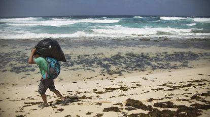 Un hombre carga con basura en la playa del Ámbar (Gran Canaria).