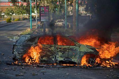 Un coche de policía israelí en llamas, tras una manifestación contra la ofensiva de Israel, este martes en la ciudad de Lod, al sur de Tel Aviv.