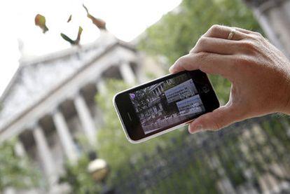 Un usuario utiliza una aplicación de Realidad Aumentada frente a la Biblioteca Nacional, en Madrid.