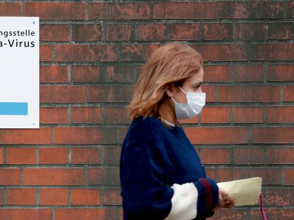 A woman, wearing a face mask, walks past a sign guiding people to the entrance of a corona testing station at the Vivantes Wenckebach hospital in Berlin on March 13, 2020. - German Chancellor Angela Merkel called on organisers of non essential events gathering hundreds of people to cancel them to help slow the spread of coronavirus. The regional governments of Germany's 16 states will decide if they want to shutter school gates according to the local situation, Merkel said on March 13, 2020, adding that an option could be to bring forward April's Easter school holidays. (Photo by Odd ANDERSEN / AFP)