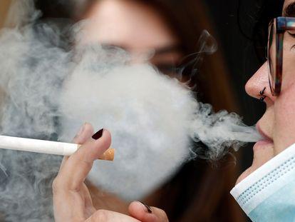 Una mujer fuma en una calle.