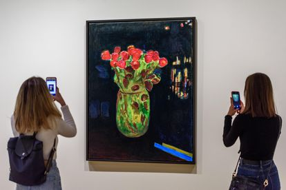 Dos visitantes fotografían la obra 'Übernachtung in Nairobi', de Caro Niederer, en la exposición 'Womanology'.