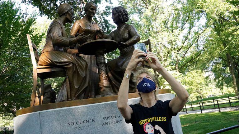 Una mujer se hace una foto frente a una estatua que honra los derechos de la mujer, entre ellos el derecho al voto, en Central Park.