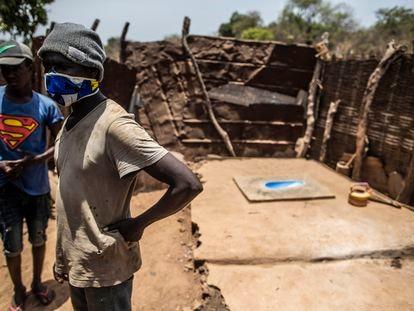 Unos vecinos de Bafatá (Guinea-Bisáu) muestran el retrete que han construido en su vivienda.