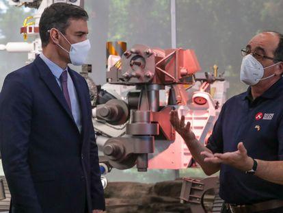 Pedro Sanchez escucha al español Manuel de las Torres, ingeniero espacial de la NASA, frente a una réplica del Perseverance, el último vehículo enviado a Marte.