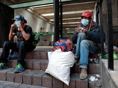 Personas sin techo usan mascarillas afuera del metro en Ciudad de México.