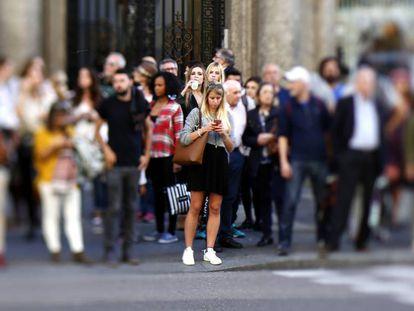 Una mujer joven consulta su móvil mientras espera en un semáforo.