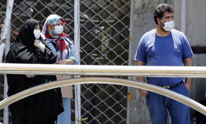Dos mujeres y un hombre con mascarilla en Teherán, capital de Irán.