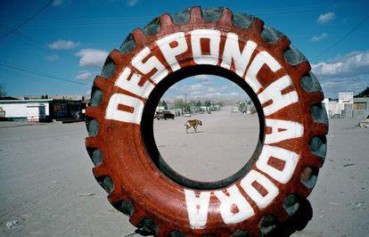 Escena en Ciudad Juárez (México). La palabra 'desponchadora' (recauchutados) pintada en el neumático anuncia un taller mecánico.