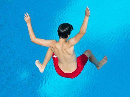 Niño, saltando a la piscina.