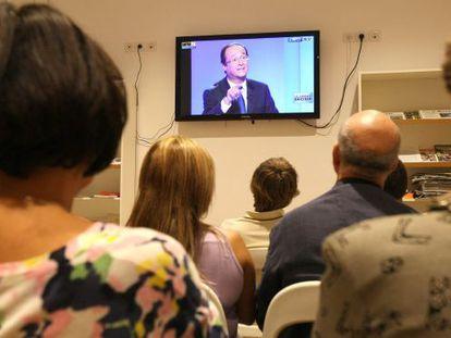 Un grupo de miembros del PS francés sigue el debate de primarias en Marsella. En la pantalla, el candidato François Hollande.