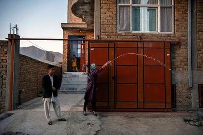 Una familia despide el 1 de junio pasado en Kabul a los que parten, derramando agua para que su camino sea luminoso y vuelvan pronto.