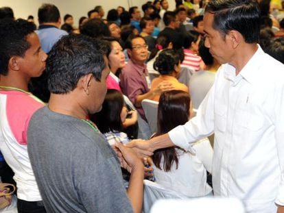 El presidente indonesia, Joko Widodo (d), dando el pésame a los familiares.