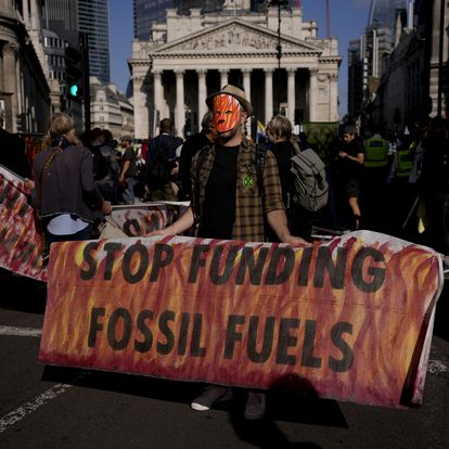 An Extinction Rebellion climate change activist holds a banner backdropped by the Bank of England, at left, and the Royal Exchange, center, in the City of London financial district in London, Thursday, Sept. 2, 2021. (AP Photo/Matt Dunham)