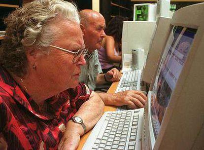 Dos vecinos de Jun (Granada) acceden a Internet en la sala de aprendizaje del pueblo.