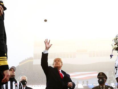 El presidente de los Estados Unidos, Donald Trump, lanza una moneda al comienzo del partido de fútbol universitario entre el Ejército y la Armada, el 12 de diciembre.