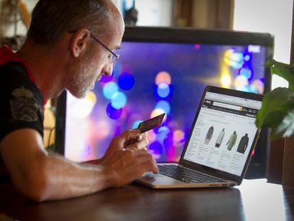 Un consumidor saca su tarjeta para adquirir productos por Internet. SANTI BURGOS