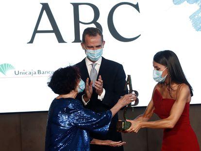 Maruja Torres recoge el premio Luca de Tena de manos de la reina Letizia mientras apalude el Rey.