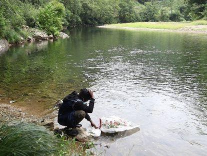 Mohame Lamine Camara, tío de Abdoulaye Koulibaly, el joven guineano ahogado en el Bidasoa, hace una ofrenda floral a su sobrino en la zona en la que este se lanzó al río.