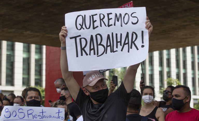 """Un trabajador de un restaurate sostiene un letrero con la leyenda """"Queremos trabajar"""", el 27 de enero."""