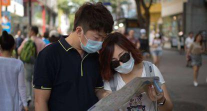 Turistas en Seúl se protegen con mascarillas este jueves.