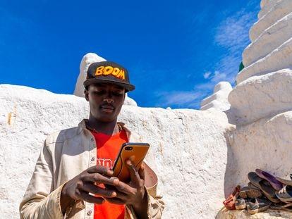 Un peregrino ormo utiliza un teléfono móvil en el santuario Sheikh Hussein, en la región etíope de Oromia.