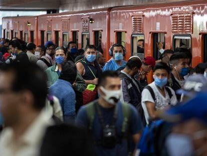 Usuarios del metro de la Ciudad de México usan cubrebocas después de que las autoridades instituyeran el uso obligatorio.